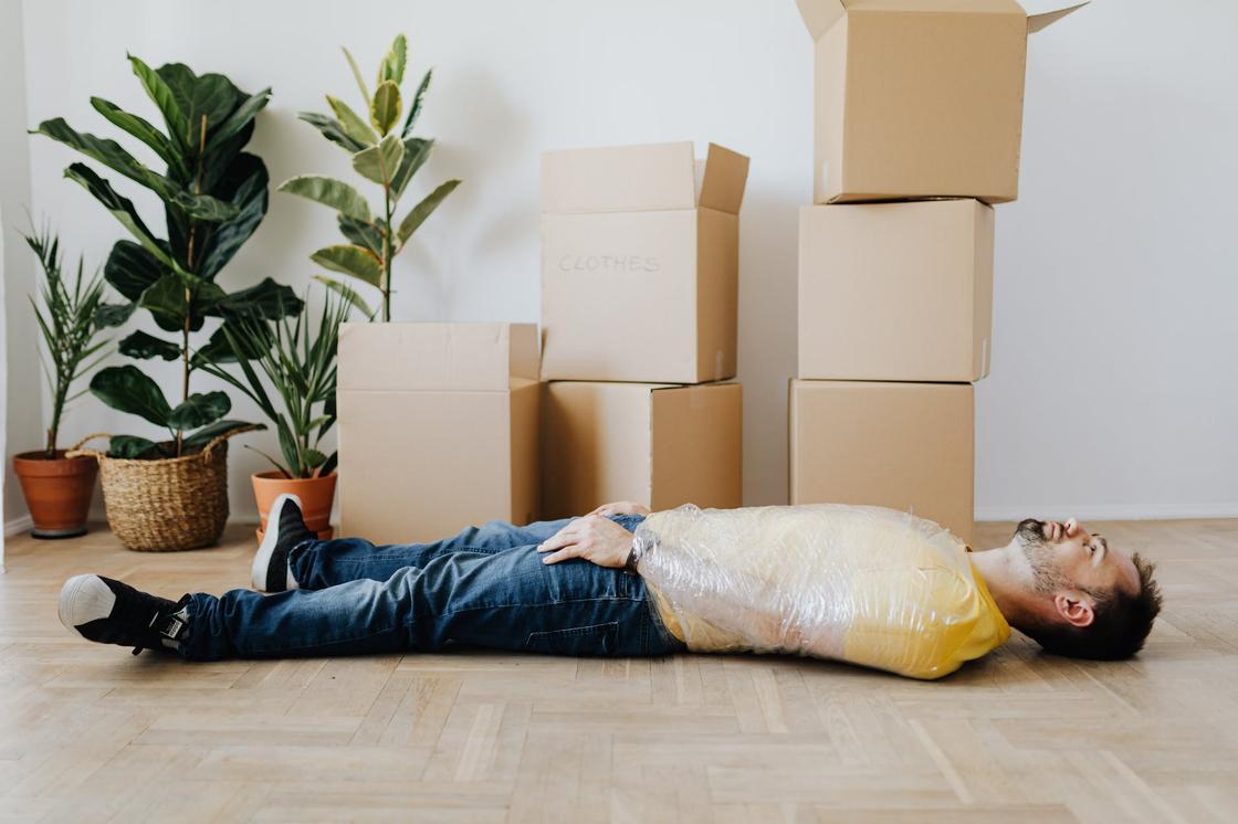 Мужчина лежит на полу рядом с пустыми картонными коробками