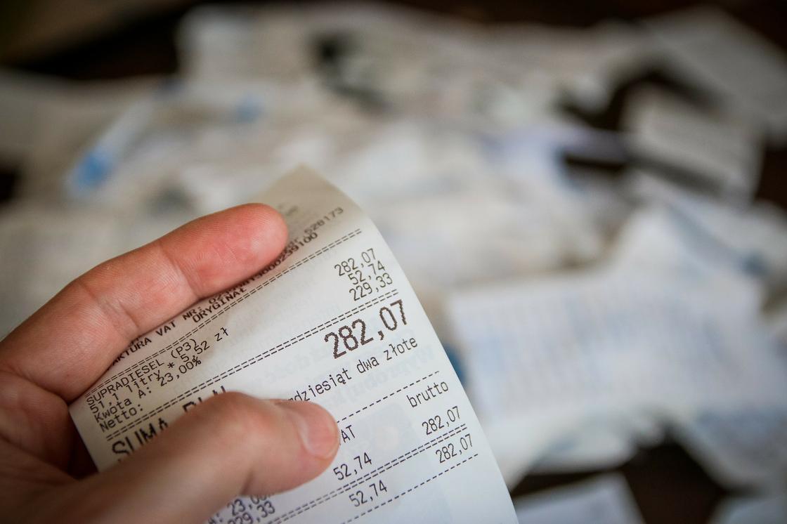 Человек держит в руке торговый чек