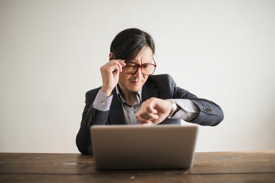 Мужчина в пиджаке сидит за столом с ноутбуком, придерживая очки и глядя на часы