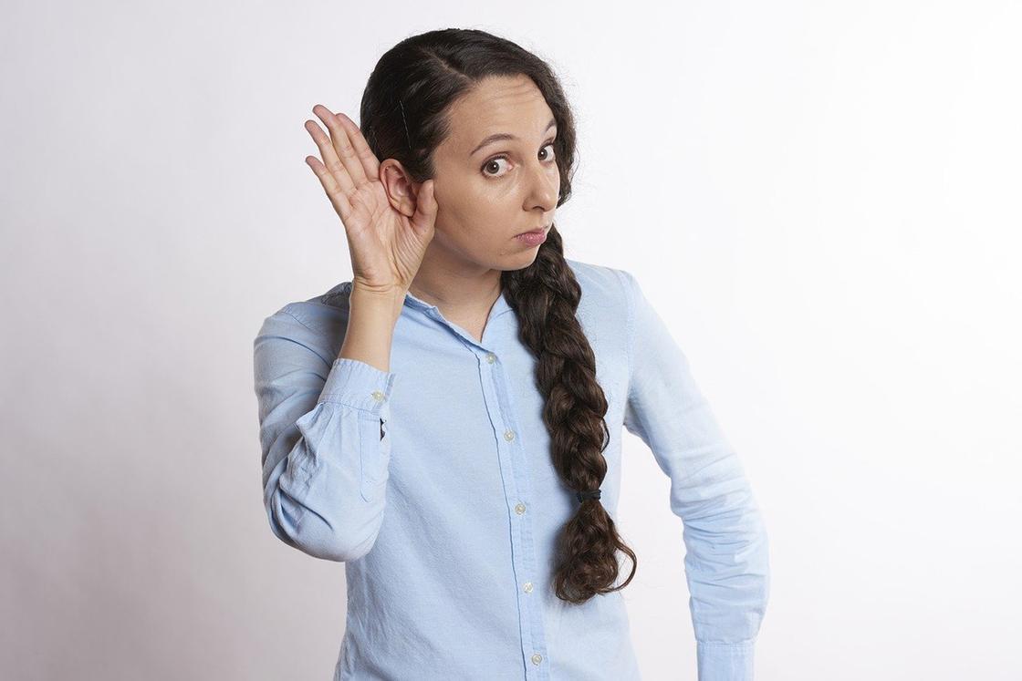 Девушка держит руку около уха