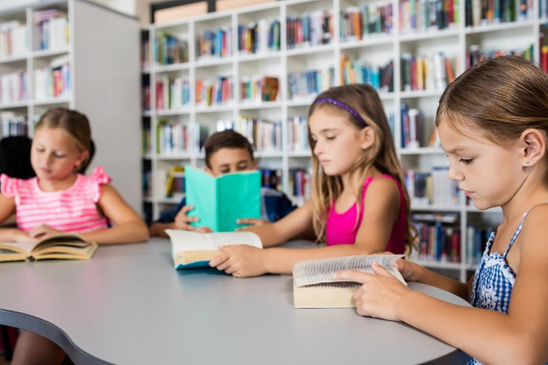 Дети читают книги в библиотеке