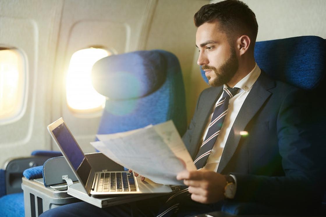 Мужчина с документами и ноутбуком в самолете