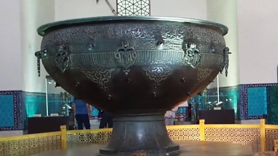 Большая металлическая чаша на ножке, украшенная резьбой, стоит в центре зала