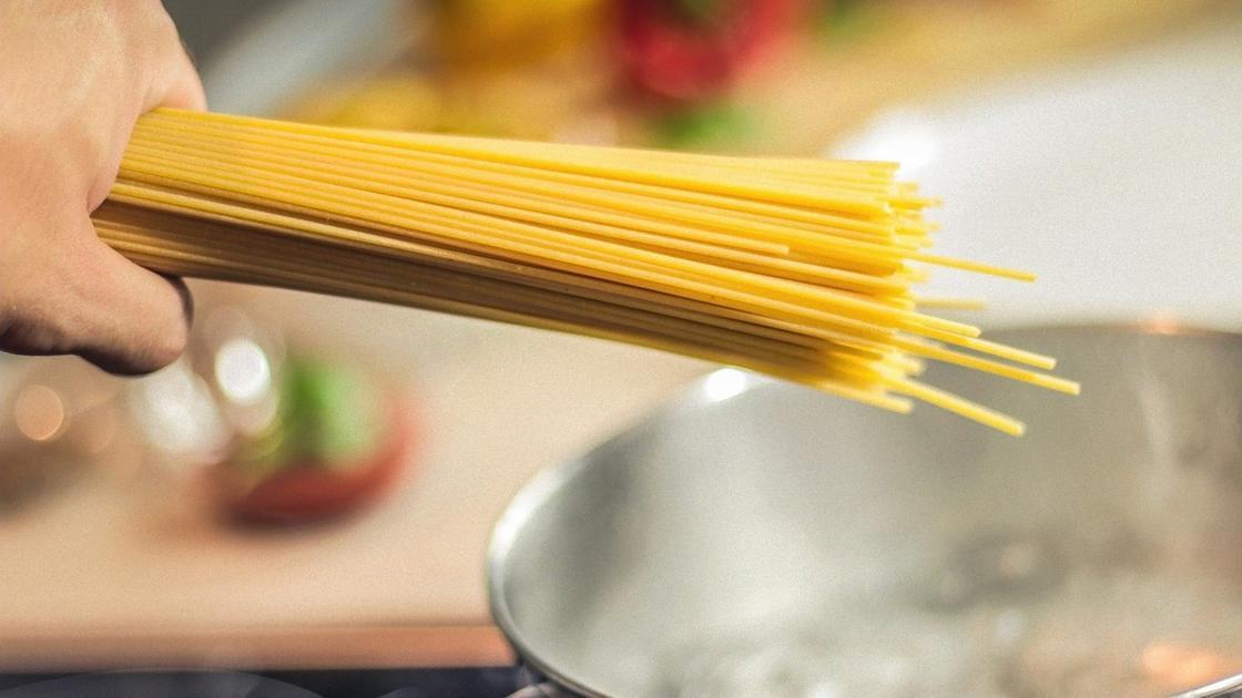 Спагетти держат в руке над кастрюлей