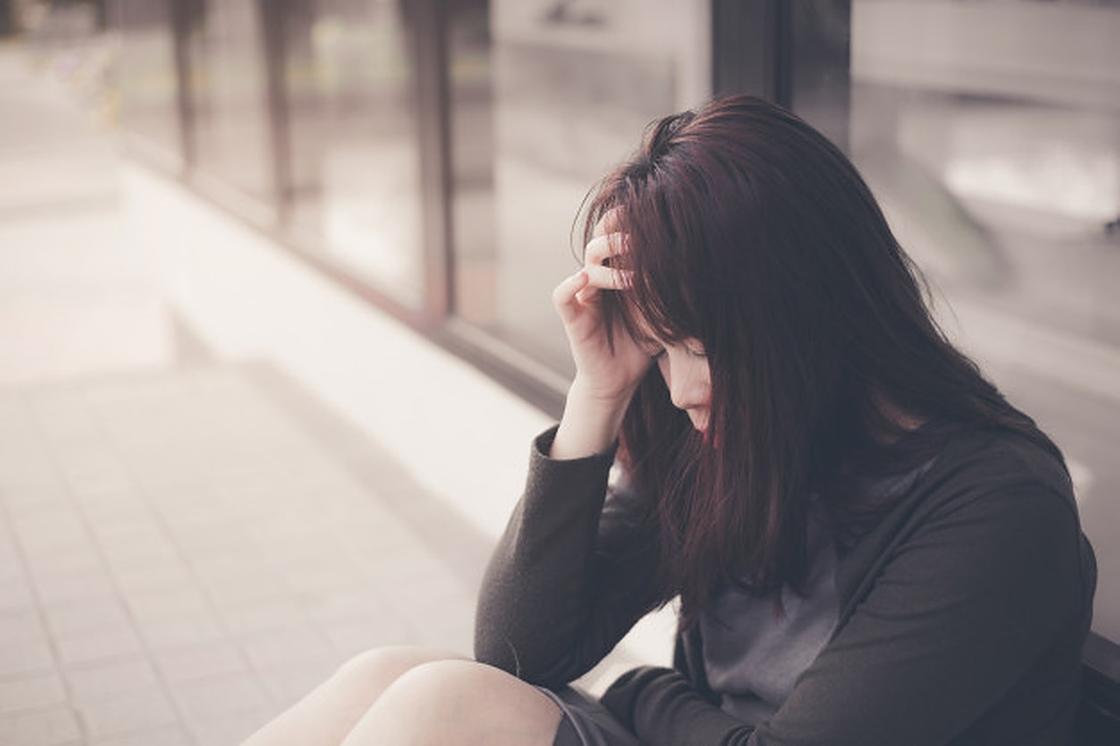 Грустная девушка сидит на улице