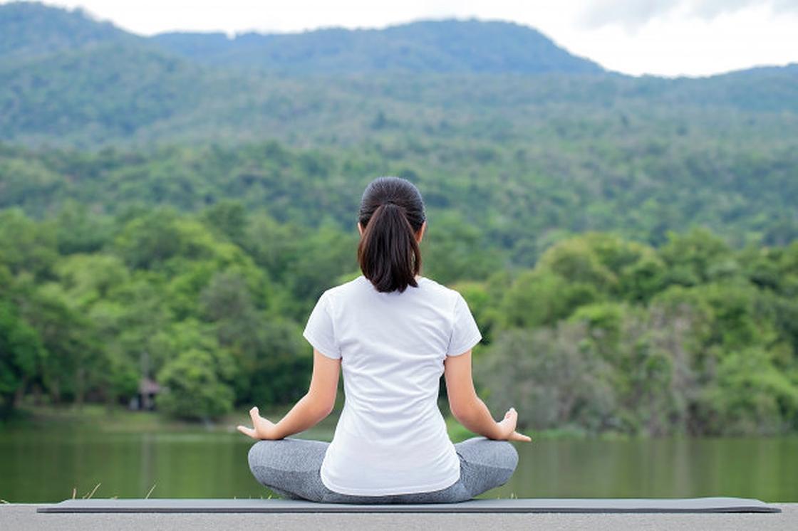 Девушка медитирует у озера в позе лотоса