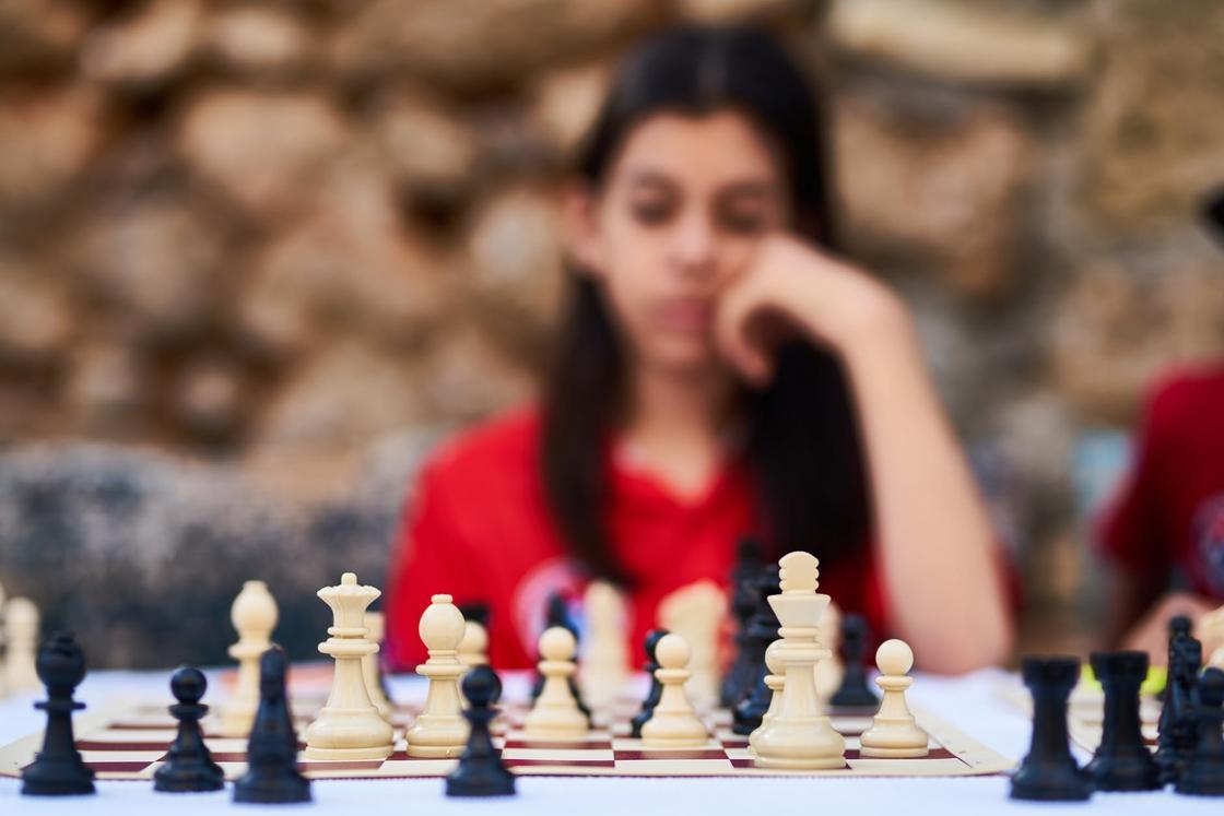 Шахматы на фоне задумчивой девушки в красной футболке