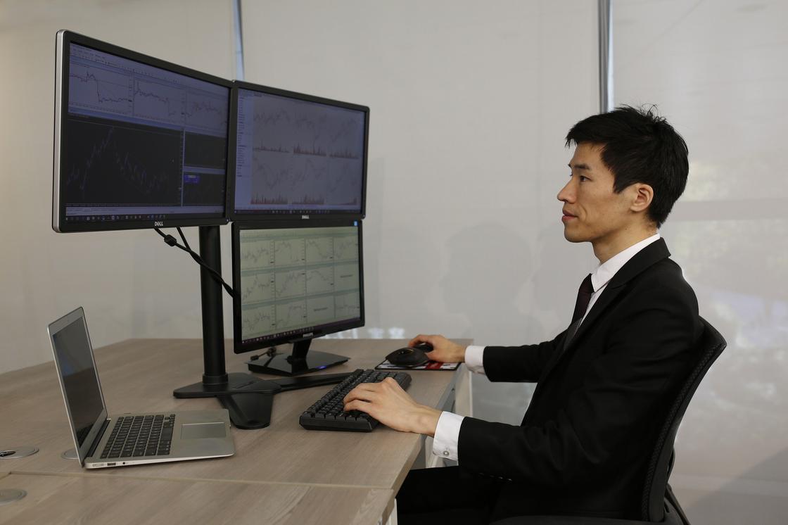 Мужчина наблюдает за тем, что происходит на компьютерных экранах
