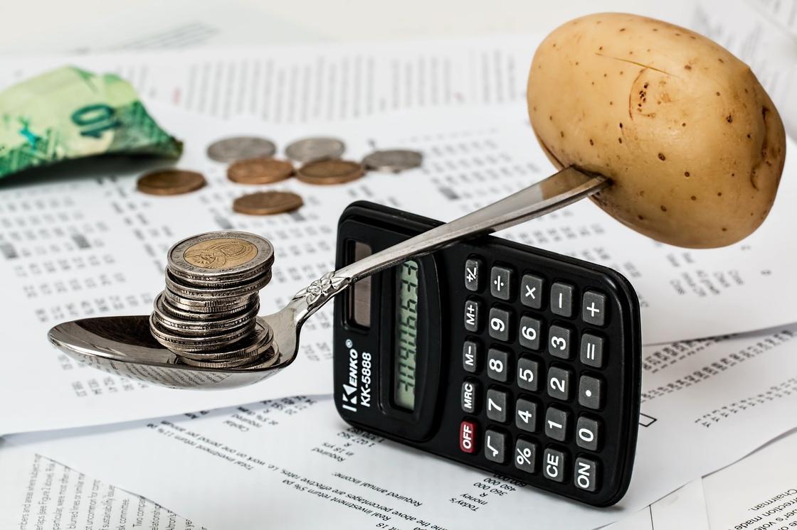 На весах из ложки и калькулятора картофель и монеты
