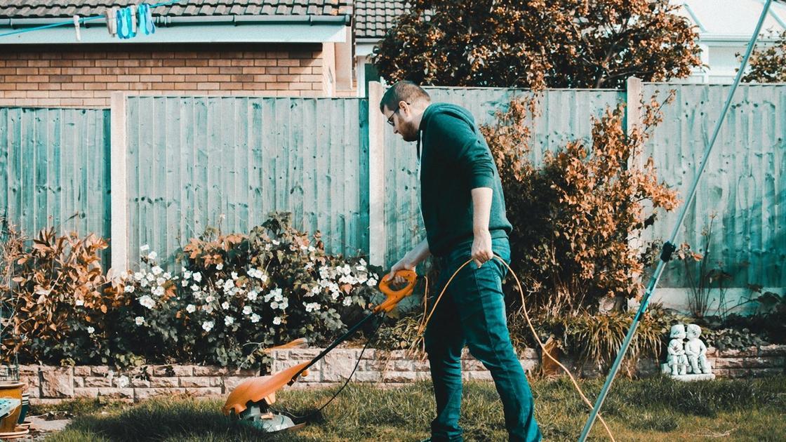 Мужчина стрижет газон ручной газонокосилкой