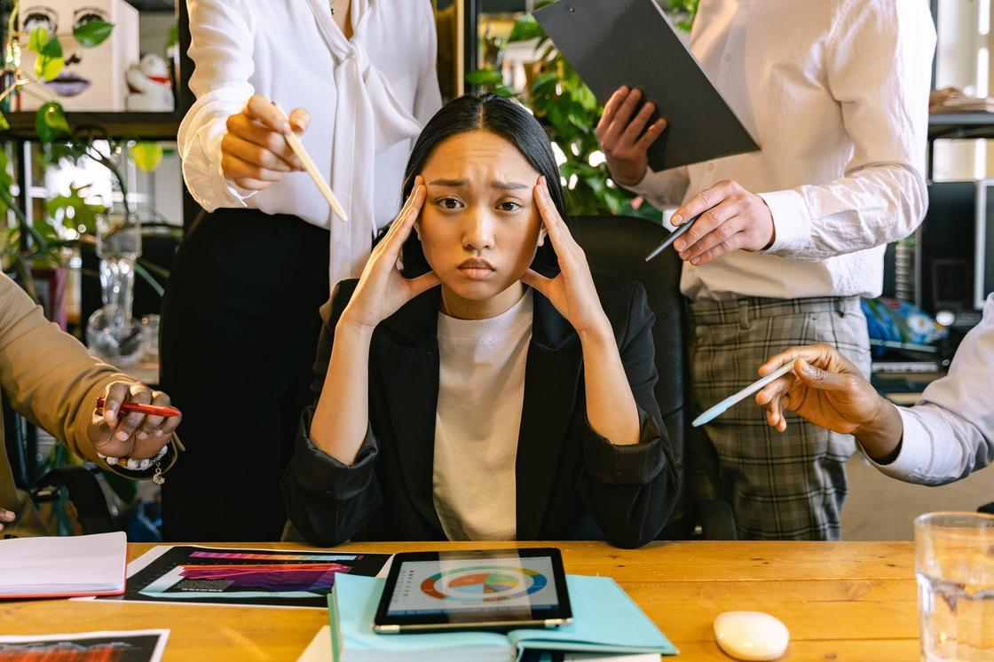 Девушка в черном пиджаке сидит за столом, держась за голову руками в окружении офисных работников