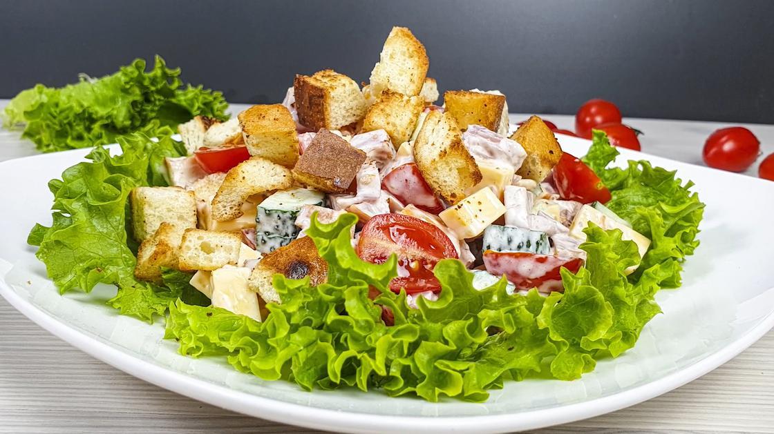 Салат «Малибу» с сухариками на белой тарелке