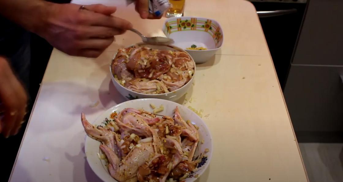 На столе тарелки с замаринованной курицей