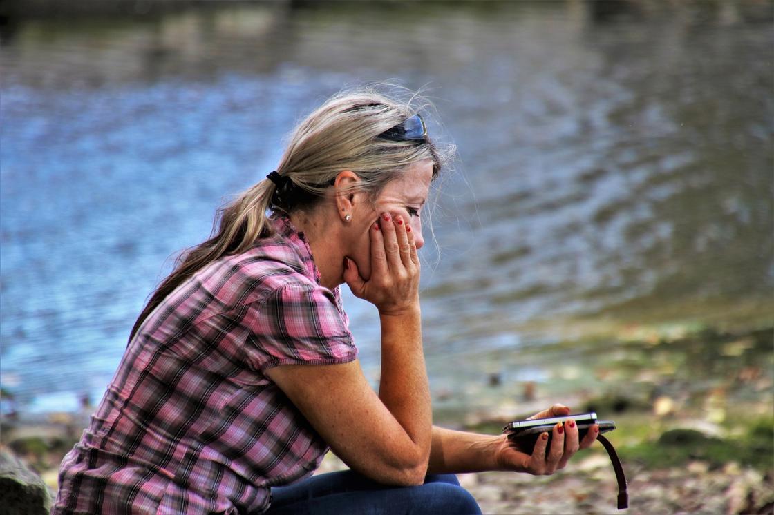 Печальная девушка сидит на берегу