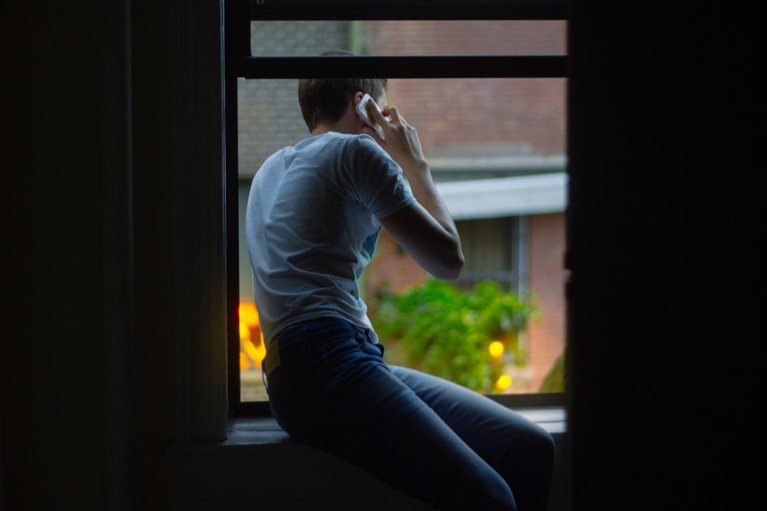 Парень говорит по телефону сидя на подоконнике