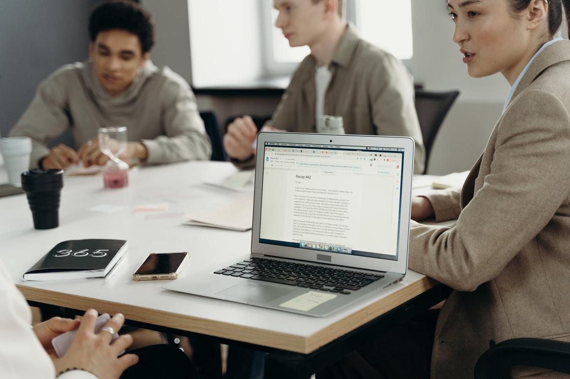 Несколько молодых людей сидят за рабочим столом и обсуждают проект