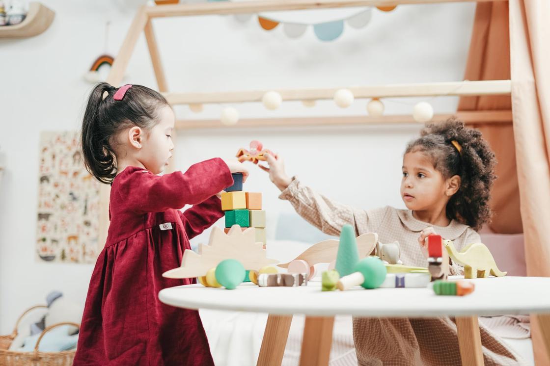 Две девочки играют цветными кубиками, сидя за маленьким столом