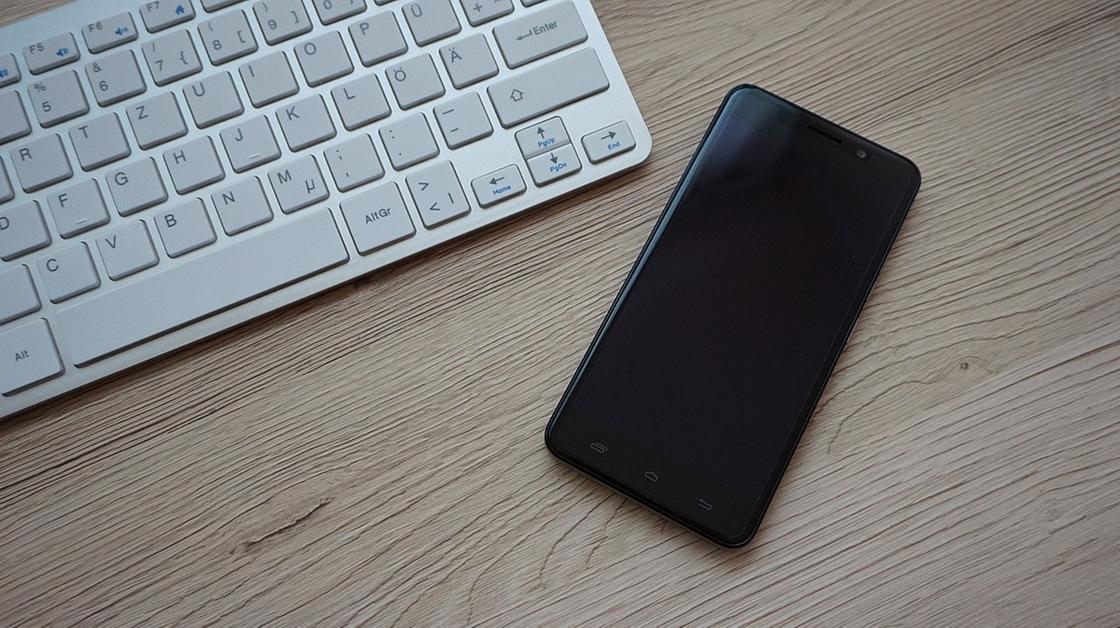 Телефон на столе рядом с клавиатурой компьютера