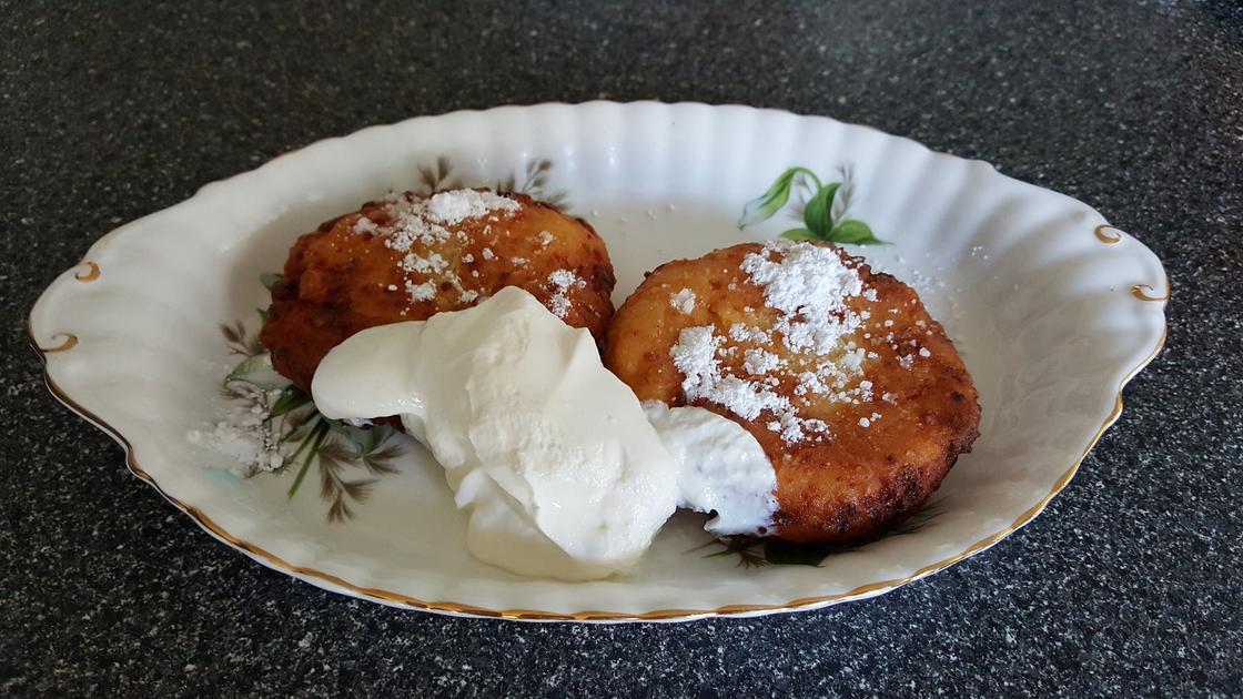 Сырники со сметаной на тарелке