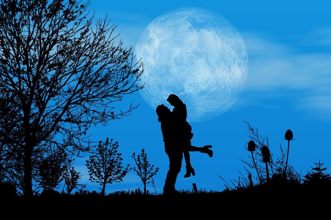 Мужчина держит на руках девушку на фоне Луны