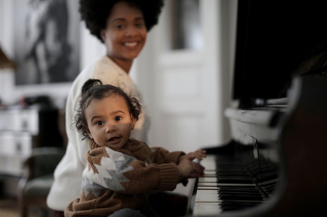 Девочка сидит за роялем рядом с мамой и смотрит в объектив