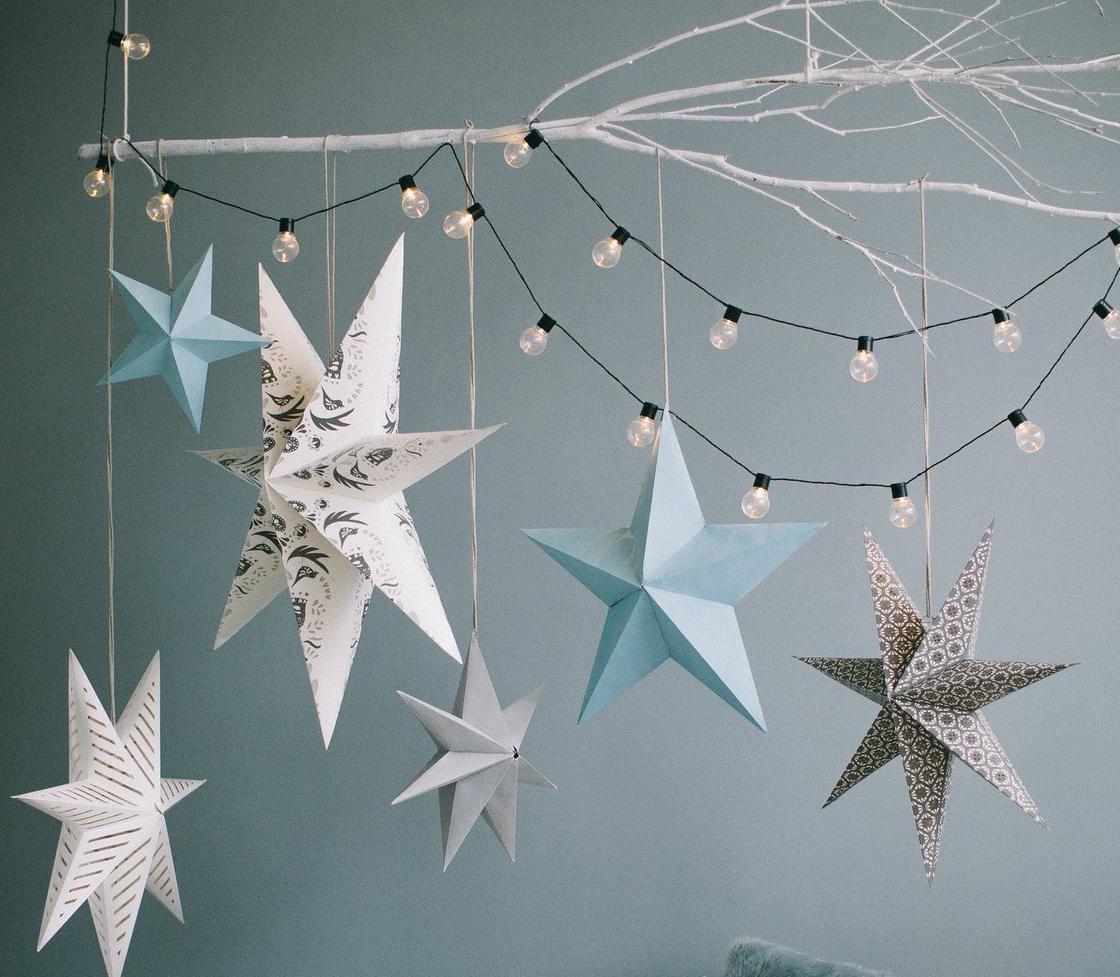 Белая ветка, бумажные звезды и гирлянда