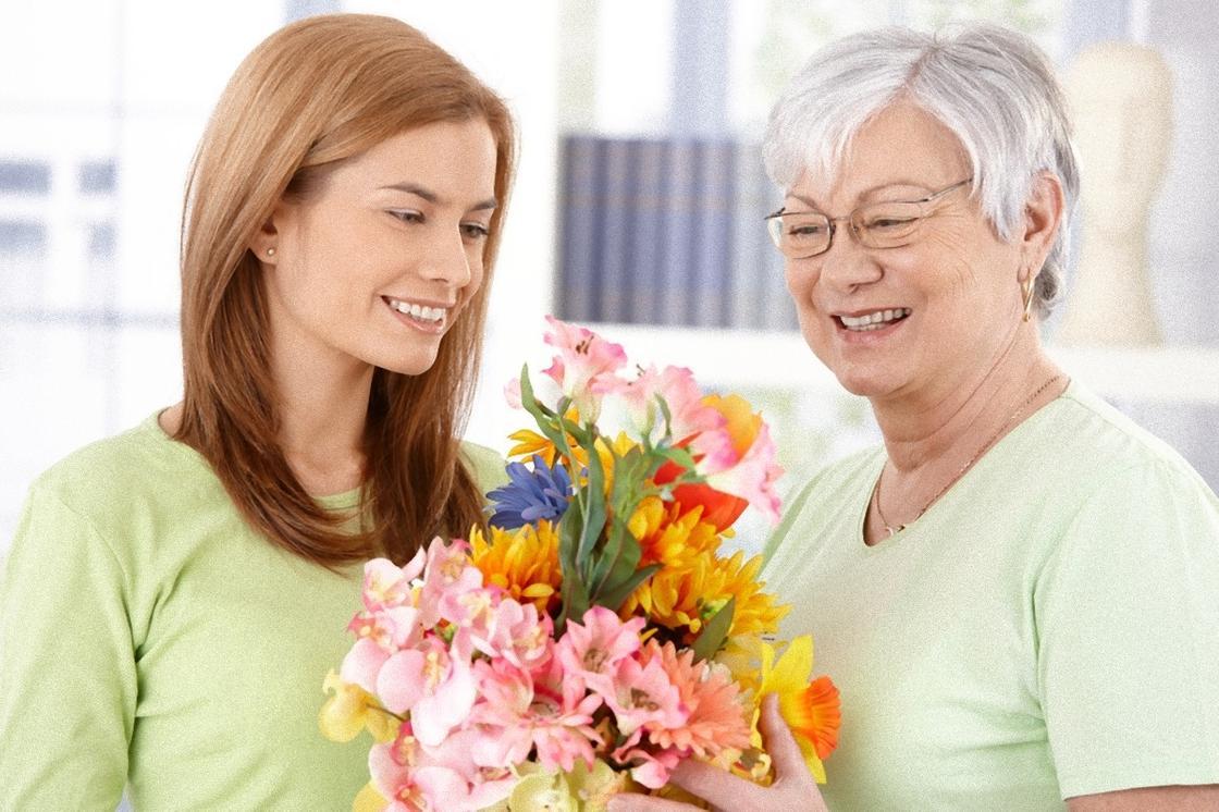 Девушка дарит цветы будущей свекрови
