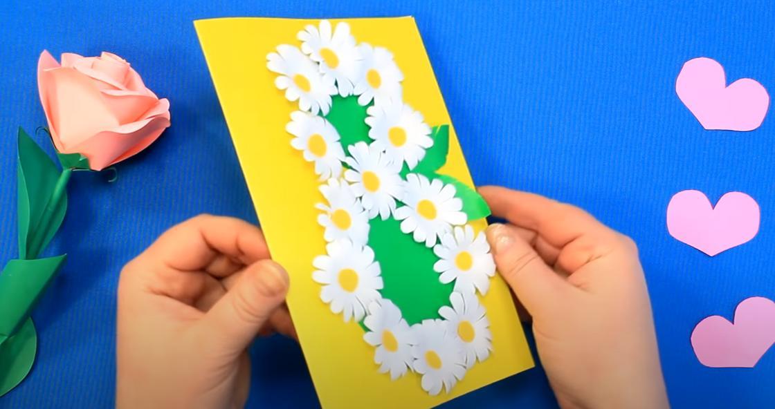 Женщина держит в руках открытку-самоделку к 8 Марта