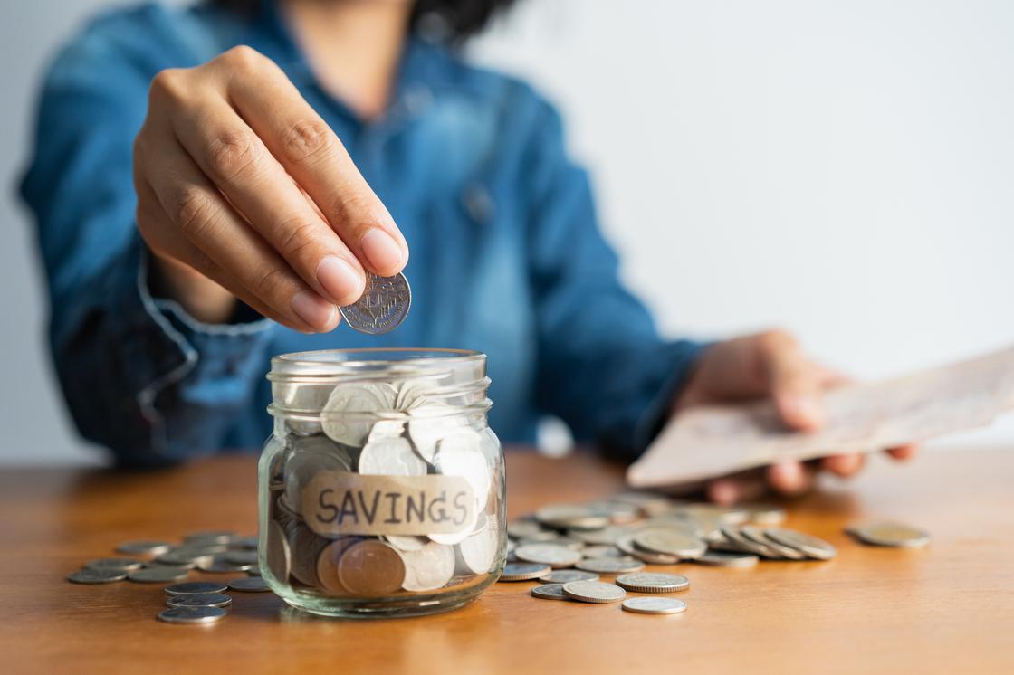 Женщина складывает монеты в стеклянную банку
