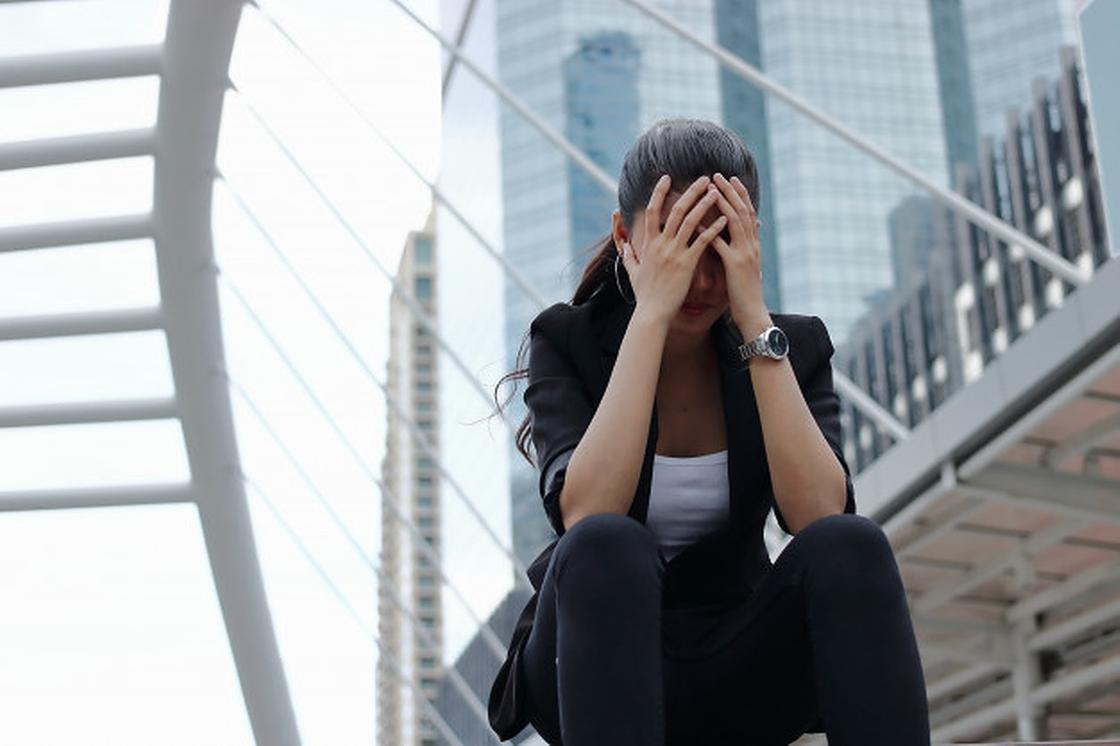 Девушка сидит, закрыв лицо руками