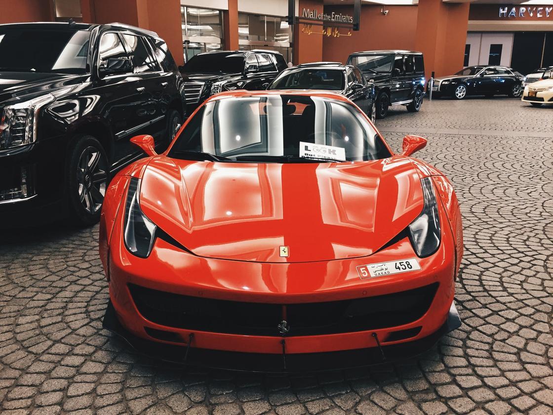 Спорткар красного цвета на фоне черных элитных автомобилей