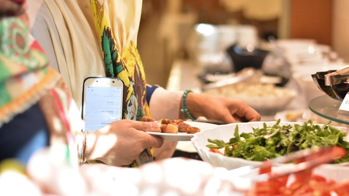 Люди накладывают еду из тарелок