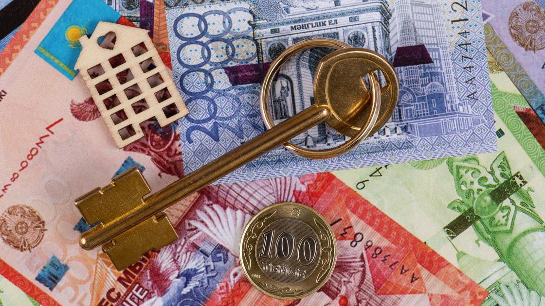 Фигурка в виде дома, ключ и монета лежат на купюрах тенге