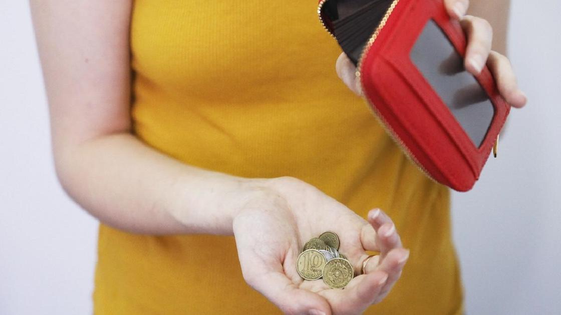 Женщина держит в руках красный кошелек и монеты