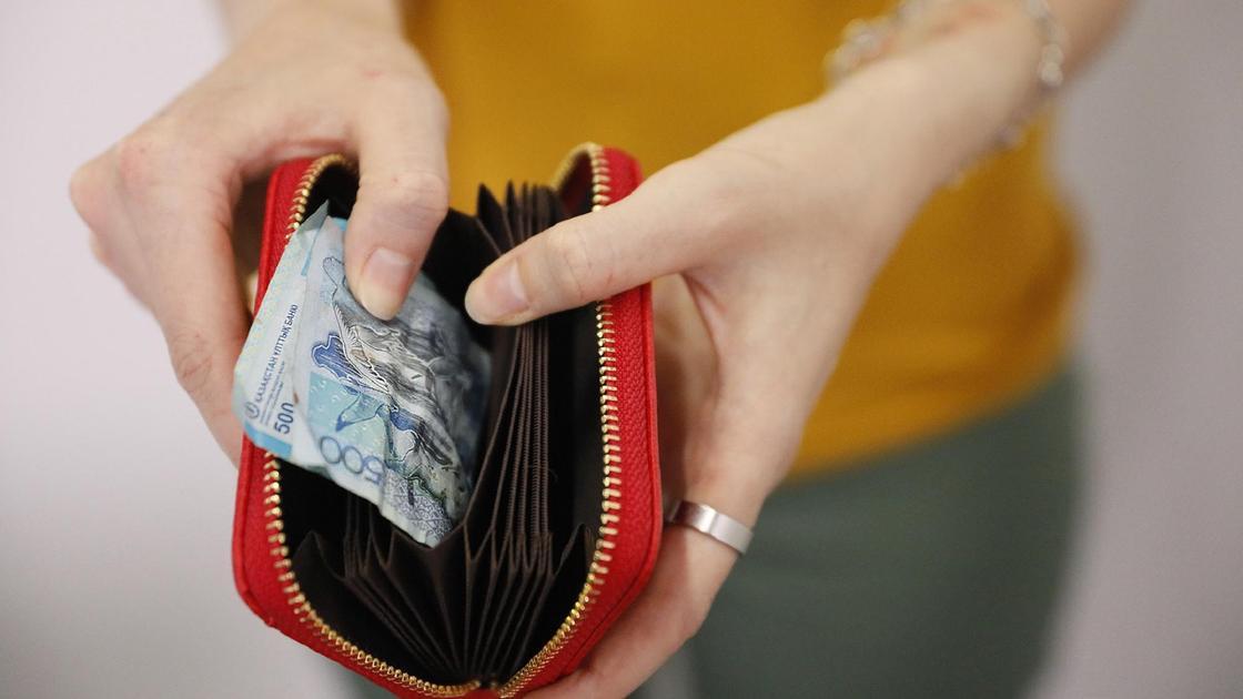 Девушка держит красный кошелек с деньгами