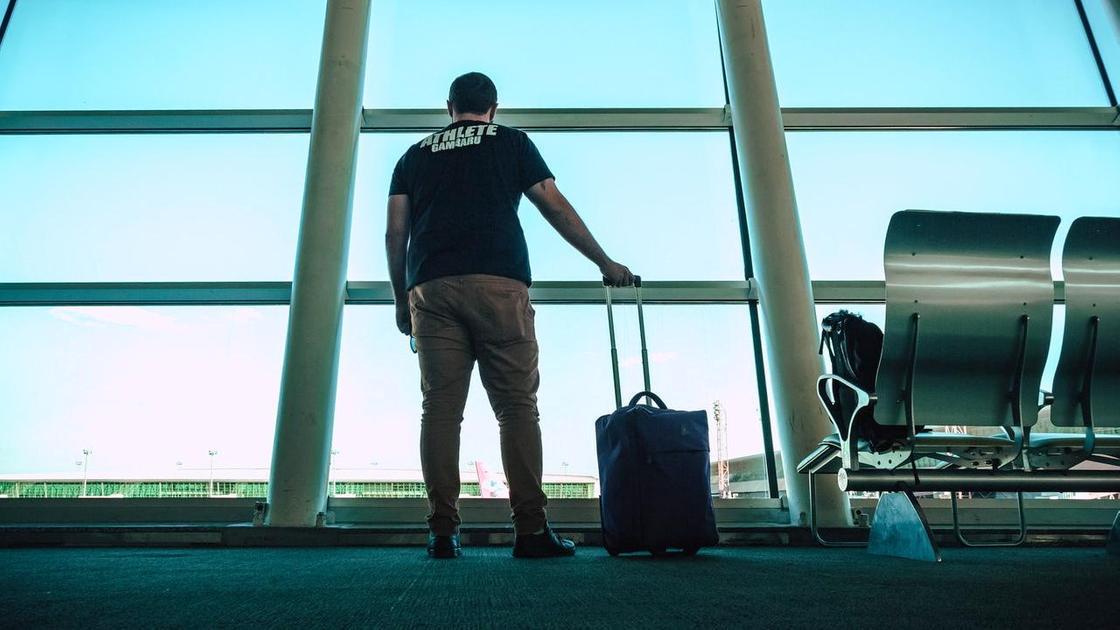 Мужчина держит сумку с вещами в аэропорту