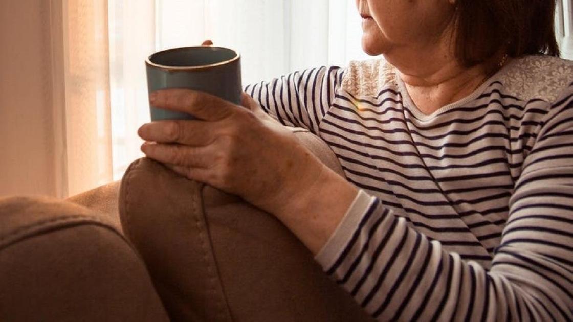 Женщина пьет чай возле окна