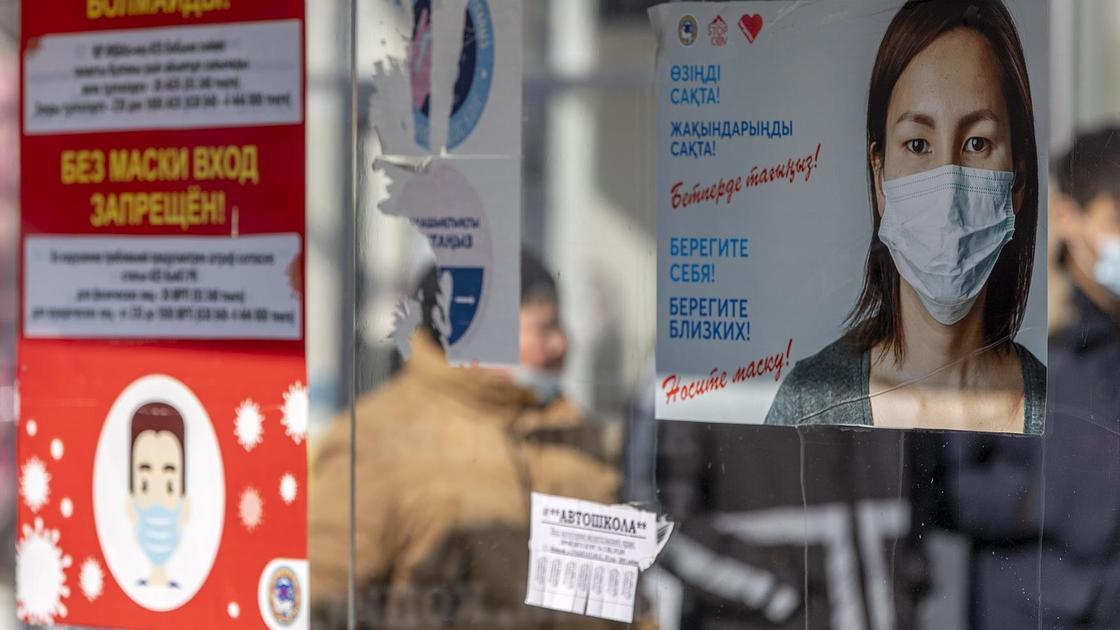 баннер с девушкой в маске висит на улице в Алматы