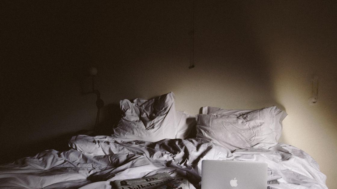Смятая постель с ноутбуком