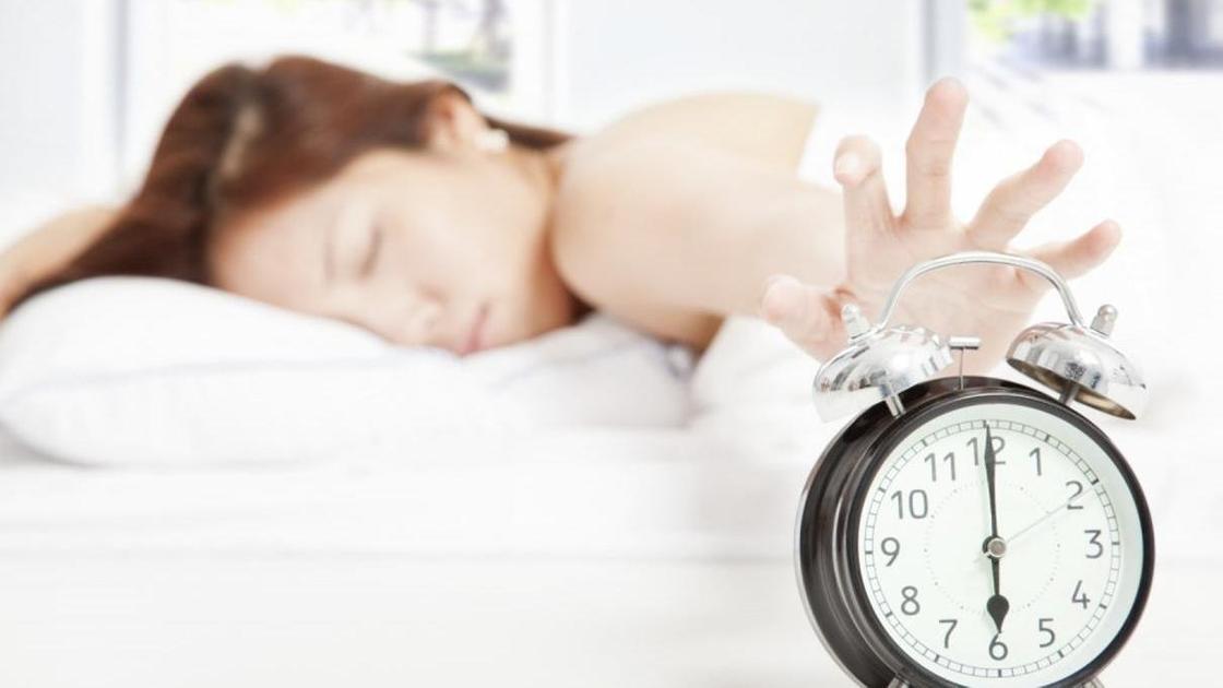 спящая девушка тянется рукой к будильнику