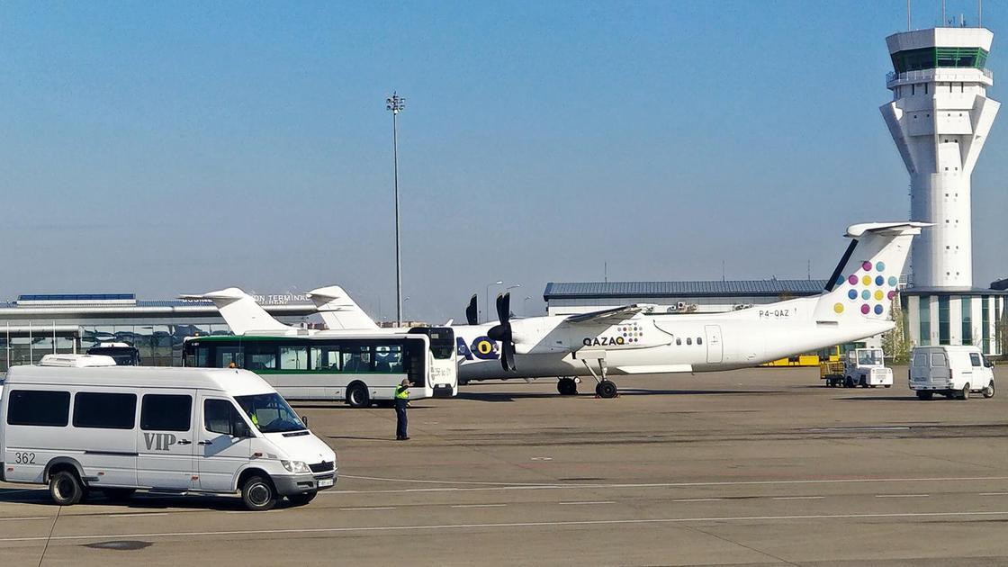 Самолеты и машины стоят в аэропорту Нур-Султана