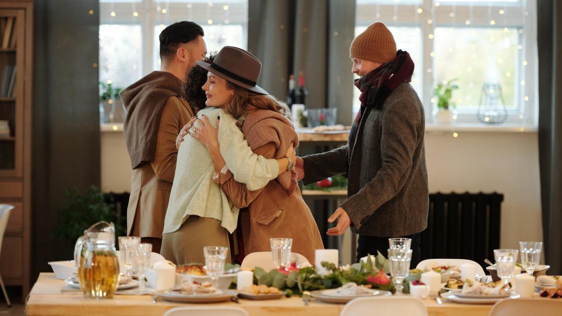 Люди обнимаются, прощаясь и поздравляя друг друга возле празднично накрытого стола