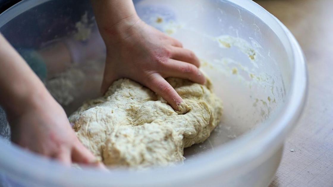 Тесто в миске месят руками