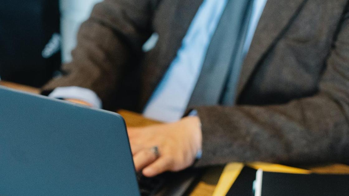 Мужчина в костюме сидит за компьютером