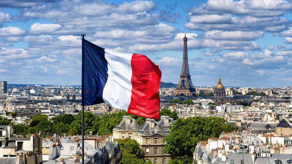 Флаг Франции на флагштоке в Париже на фоне Эйфелевой башни