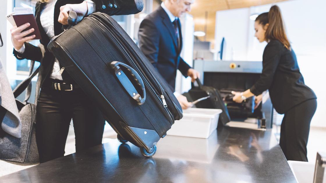Мужчина забирает свой багаж в аэропорту