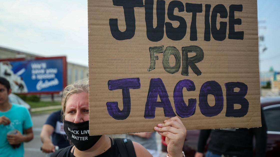 Женщина в черной маске держит плакат