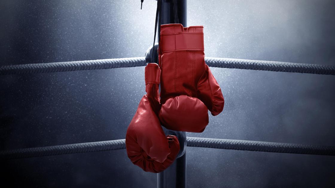 Боксерские перчатки висят на канатах