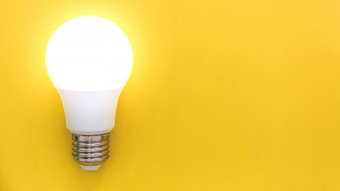 Лампочка светится на желтом фоне
