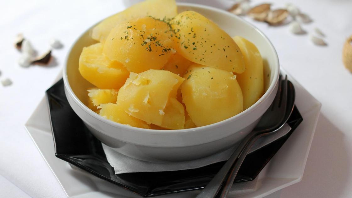 Вареный картофель в тарелке стоит на столе